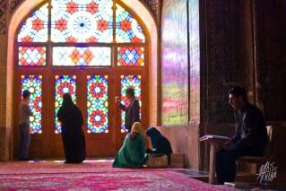 Un hombre lee el rezo en la mezquita mientras turistas se sacan foto en los vitrales.