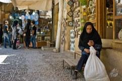 Señora manda mensaje mientras descansa luego de hacer compras en uno de los mercados de Shiraz.