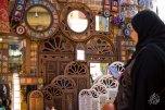 Señora mira espejos en una tienda en el gran bazar de Shiraz.